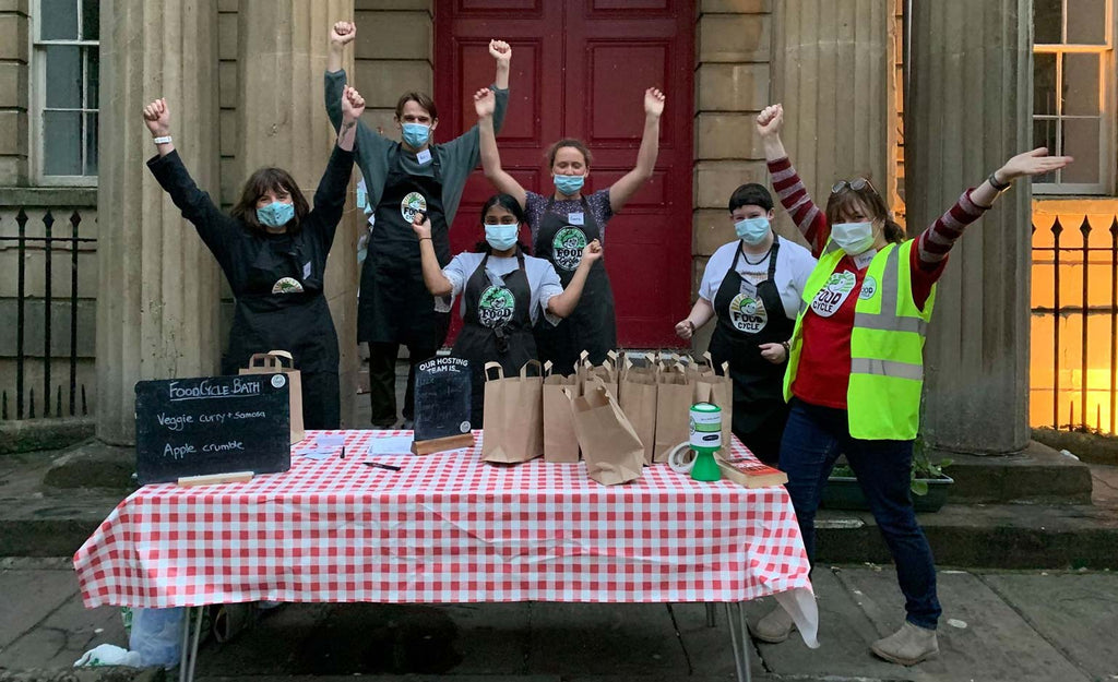 Six FoodCycle volunteers stood behind a table with a red checked cloth on it. They are all wearing masks and have their hands in the air. On the table there are paper bags of food.