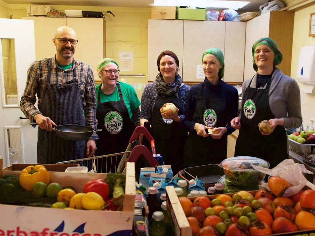 Five FoodCycle volunteers pictured in a kitchen. There is one male and four females. In front of them are boxes of fresh fruit and vegetables.