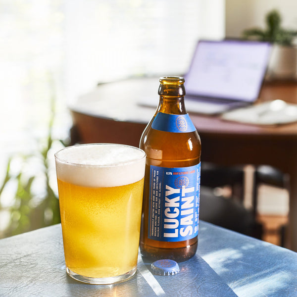 In the foreground a pint of Lucky Saint's alcohol free lager has been poured into a glass, to its right there is the branded beer bottle. The background shows a laptop on a desk.
