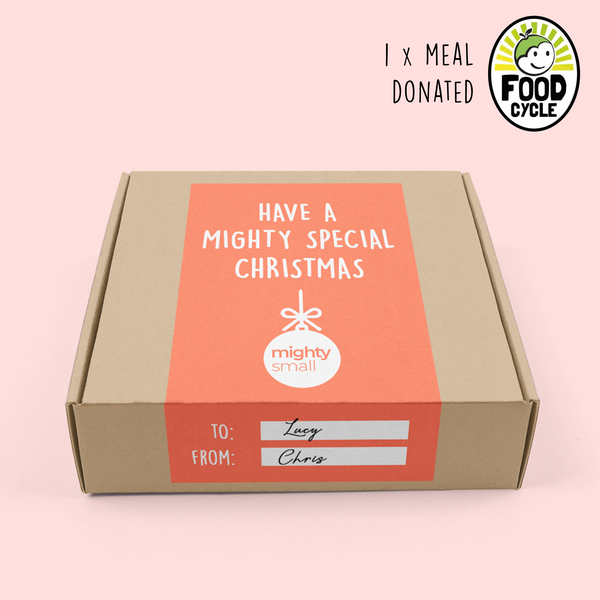 "Photo of Christmas Mystery Box - peach background with brown cardboard box with orange label. Label says 'Have a mighty special Christmas' and features a to and from section. Black, white and green FoodCycle logo in the top right hand corner - saying ""1x meal donated""."