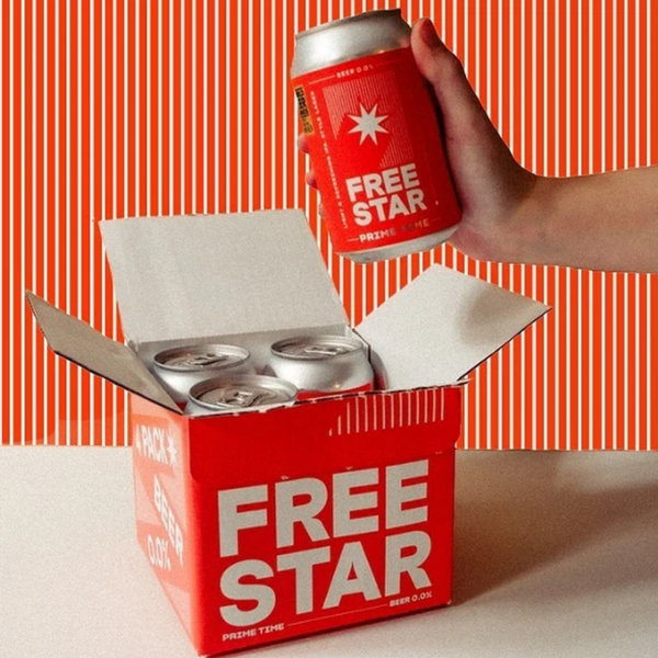 Striped red and white background with Freestar's box of 4 alcohol free beers in the foreground. On the right of the photograph, a hand holds up one of the non-alcoholic beers.