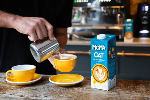 A barista pours Moma Barista Style Oat milk into a yellow coffee cup using a metal jug.