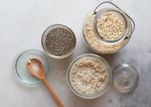 Several glass jars and bowls filled with porridge and chia seeds.