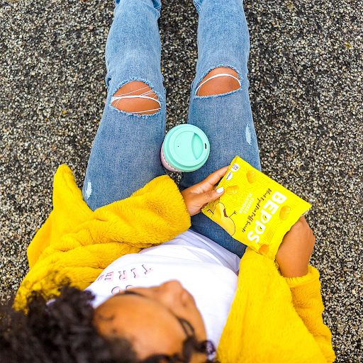 A lady in a bright yellow coat digs into a pack of Bepps crisps.