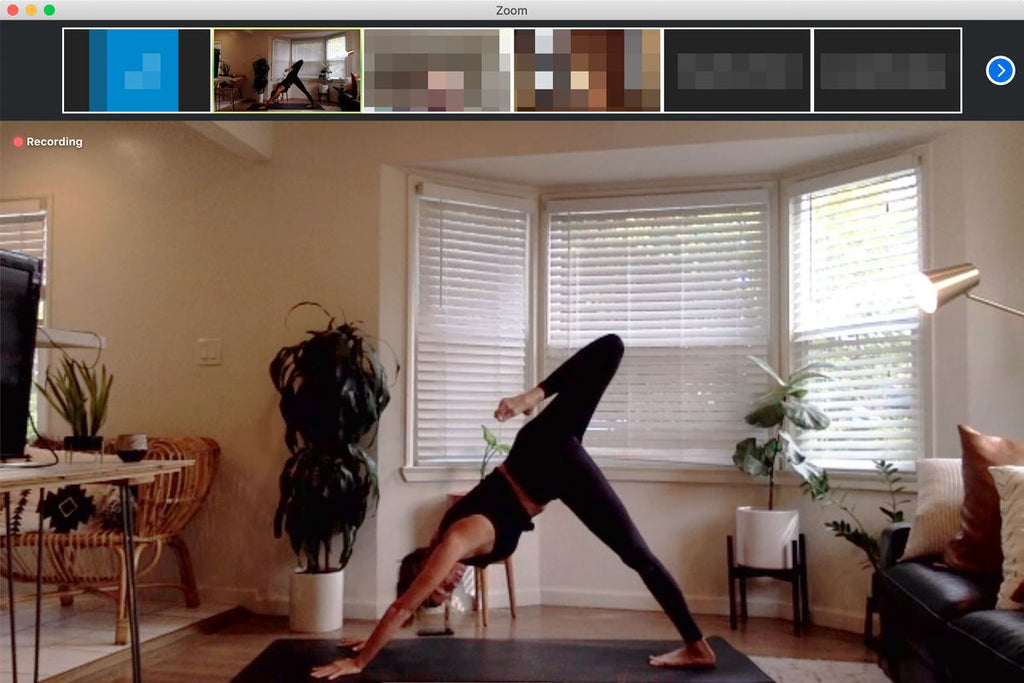 Zoom yoga class taking place in a Woman's living room. She is wearing black and is posing in downward dog. There are 4 plants in shot as well as her large window and sofa cushions.