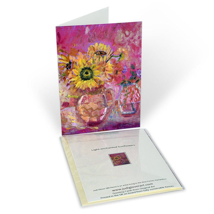 Art Greeting Card. A fine art greeting card made from original art. The original art is of sunflowers on a table in a vase. Strong yellow and pink colours. The original painting art card was painted by Judi Glover. It is available as a fine art greeting card at Judi Glover Art.