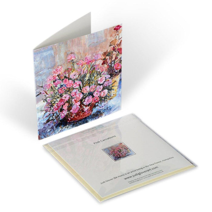 Showing the art greeting card standing up and the back of the carnation card laying flat. Each floral greeting card by Judi Glover Art is blank with envelopes and measures 6 x 6 inches