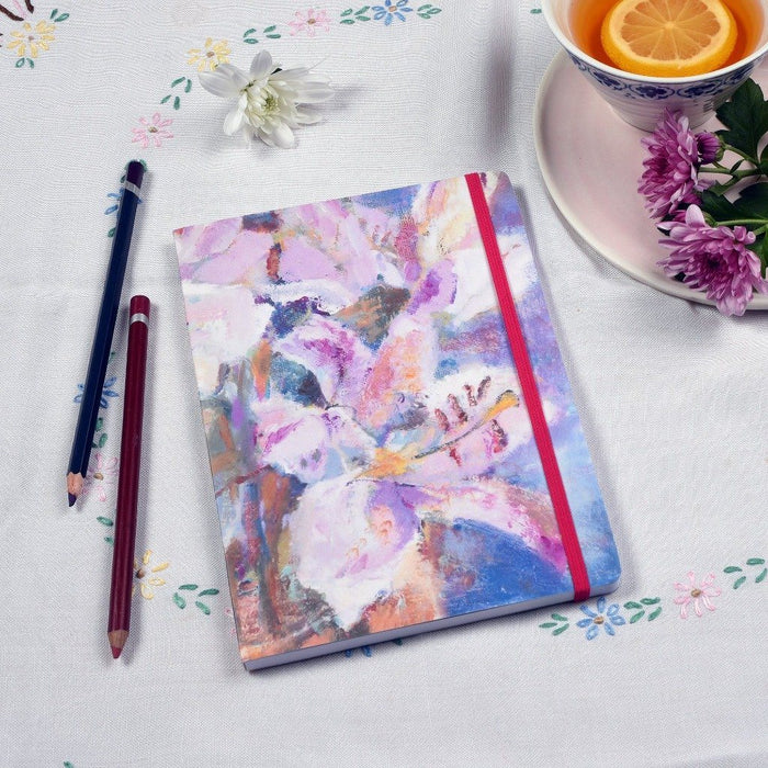 Picture showing the lilies notebook on a table. You can see the pink elastic enclosure which matches the floral notebook