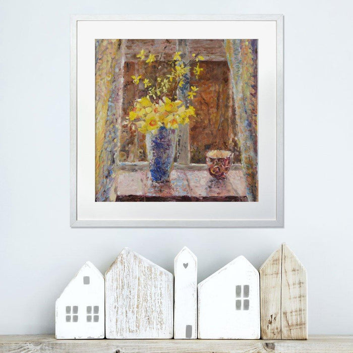 Daffodil Prints from a fine art painting by Judi Glover Art of Spring Daffodils in a vase next to a window. The Daffodil Wall Art Print is framed in white and hanging on a wall above a shelf with wooden houses