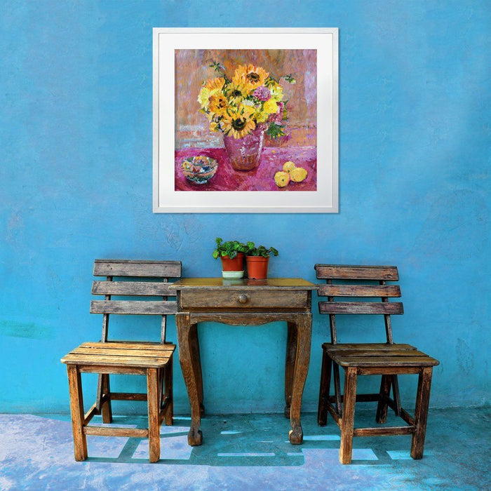 Sunflower prints showing bright sunflowers in a vase on a table with a pink cloth. The sunflower art print is framed on a wall above a table and chairs. The sunflower wall art is available from Judi Glover Art