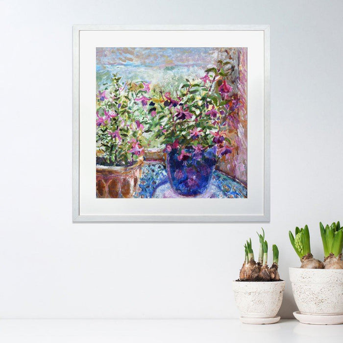 Flower art prints with two pink fuchsias with their fairly flowers. The fuchsia wall art is framed in a white frame and hanging on a wall and available at Judi Glover Art