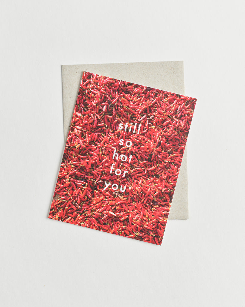 "Photo greeting card of a bed of red chili peppers and white words ""still so hot for you""."