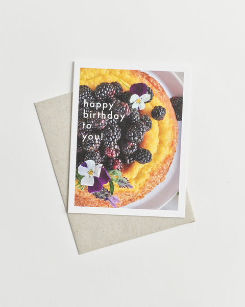 "Photo greeting card of a round yellow cake topped with deep purple berries and flowers and white words ""happy birthday to you!"""