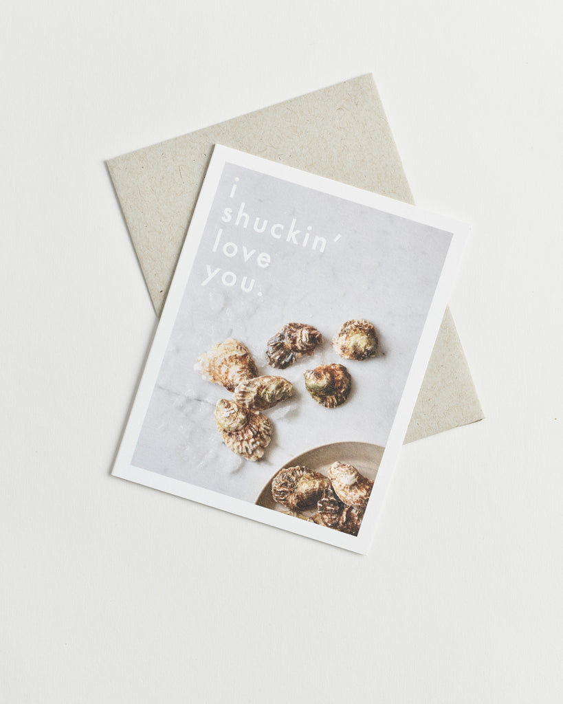 "Photo greeting card of oyster shells scattered on a marble counter and words ""I shuckin' love you"""