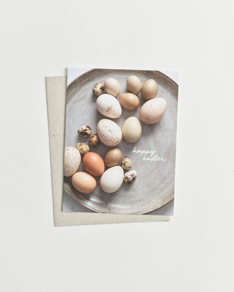 "Photo greeting card of assorted brown and white eggs in various patterns and sizes with words ""happy easter"" in cursive."