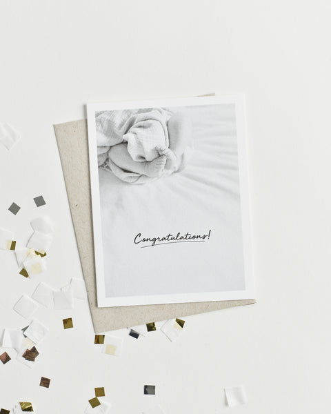 "Greeting card with a black and white photo of baby feet and ""Congratulations!"" in cursive."