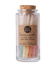 Hand-dipped beeswax candles in assorted colors with an ombre effect, packaged in a glass jar with a cork top.