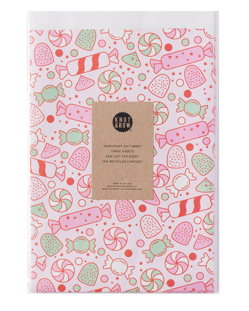 package of flat newsprint gift wrap in a pink pattern of holiday candies and sweets
