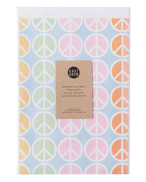 package of flat newsprint gift wrap in blue with a pattern of peace signs in various colors