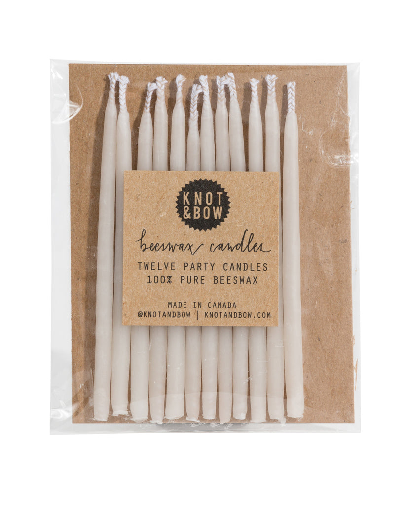 Package of 12 tall hand-dipped beeswax birthday candles in ivory white.