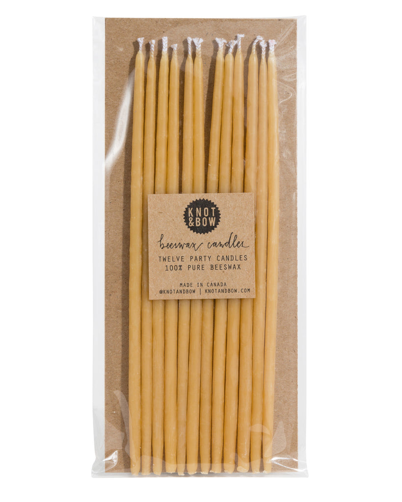 Package of 12 tall hand-dipped beeswax birthday candles in a natural pale yellow color.