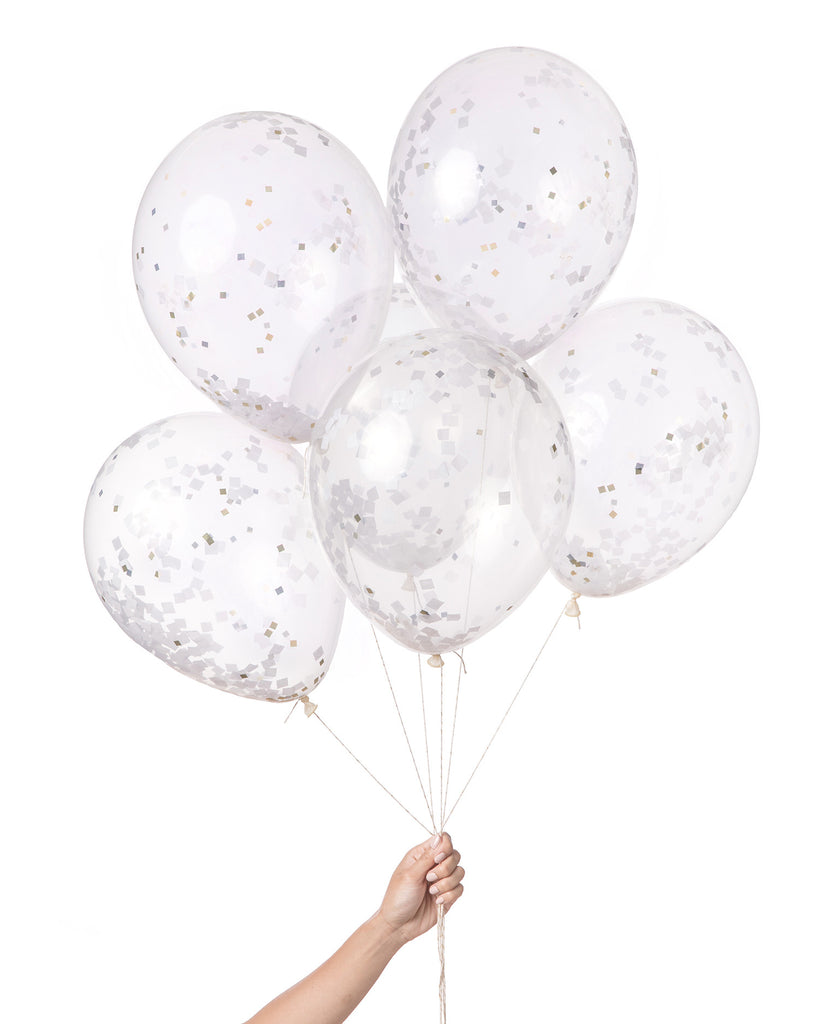 Bunch of clear balloons filled with white and metallic gold and silver confetti