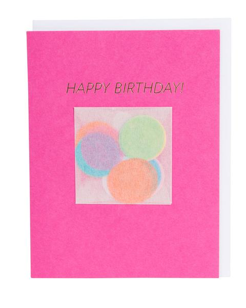 "Greeting card in hot pink featuring assorted rainbow confetti and ""Happy Birthday"" in foil lettering."