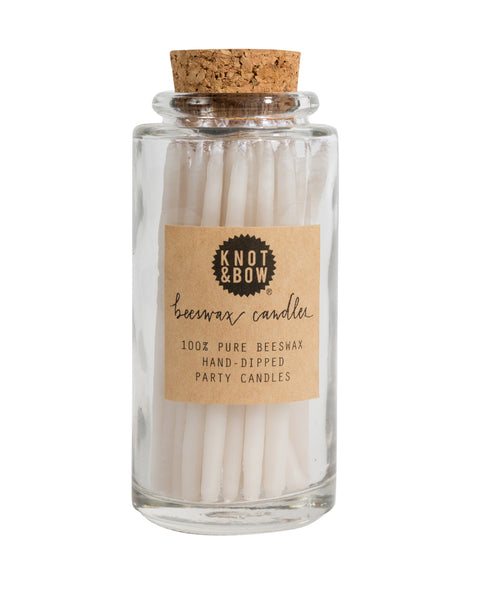 Hand-dipped beeswax candles in ivory white, packaged in a glass jar with a cork top.