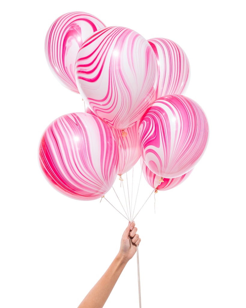 Bunch of pink and white party balloons with a marble effect.