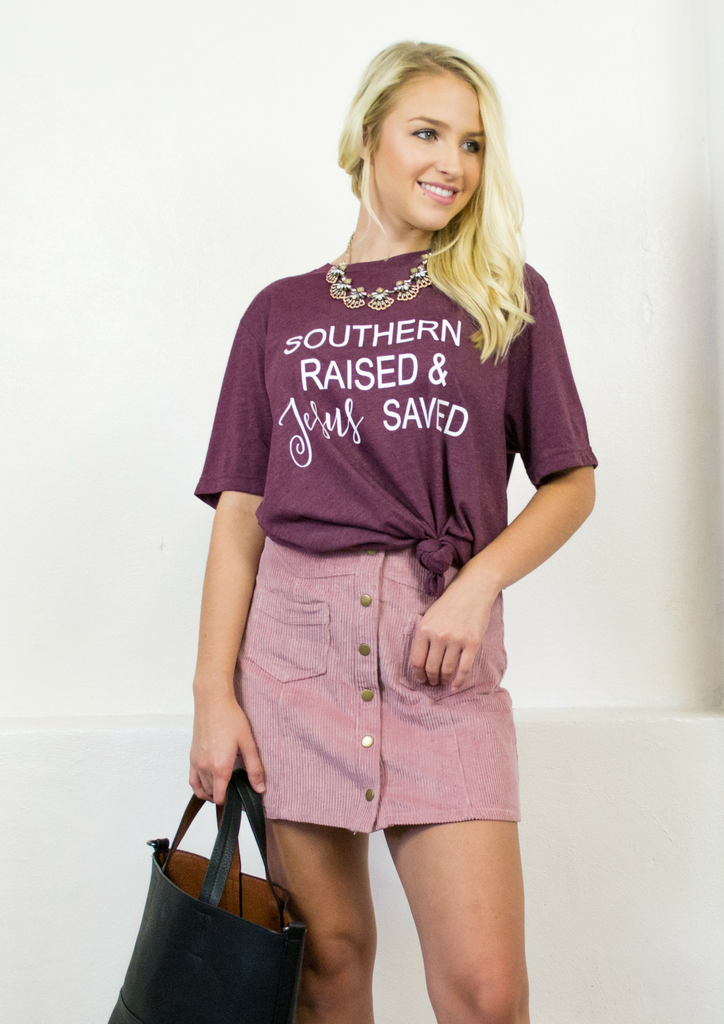 suede pink skirt with a blag purse and a red graphic tee