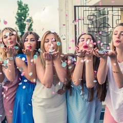 An image of a group of women blowing confetti at the camera.