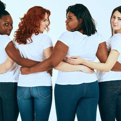 An image of four girls all wearing white t-shirts and jeans.