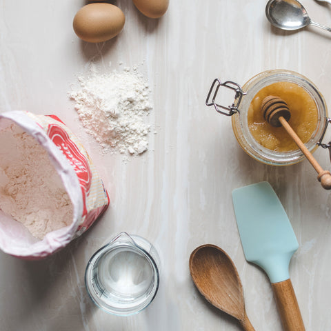 Flour, mixing bowl, baking utensils and eggs on a table