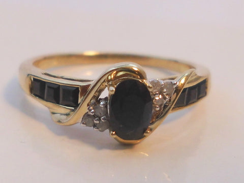 Sapphire & 9ct Gold Cluster Ring    Set with oval cut dark sapphire to centre
