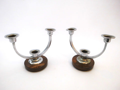 Pair of Art Deco Candle-stands. Each with circular dark brown wooden Support and 3 chromed Candleholders.