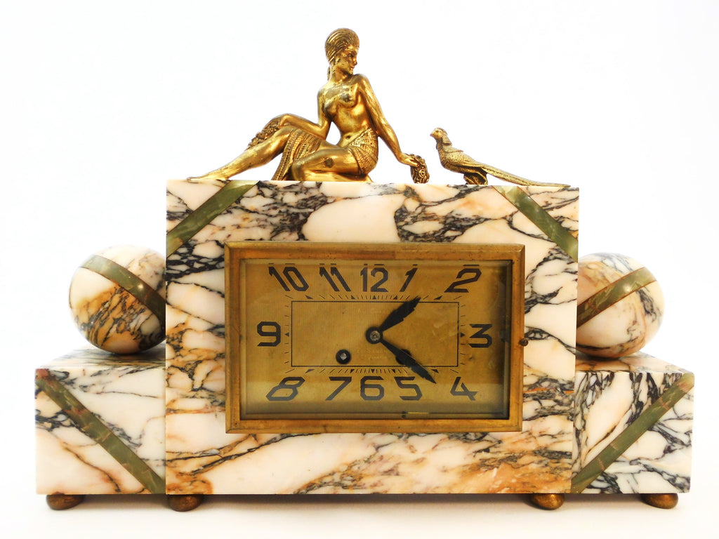Mantel Clock in Marble with Figurines in brass alloy (messing/laiton) on top of a Lady feeding a Pheasant. Eight-day clock movement with chime. France 1920s.