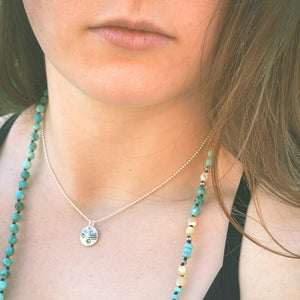 Sterling silver artisan charm on a woman's neck. Has a very boho and casual vibe.