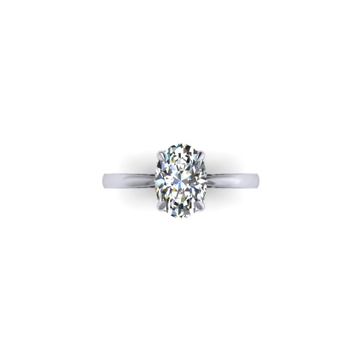 Hidden Halo with Tapered Shank Featuring Oval Brilliant This ring features an oval brilliant center stone set in a tapered pinched solitaire shank with a diamond basket that elegantly cradles the center stone.