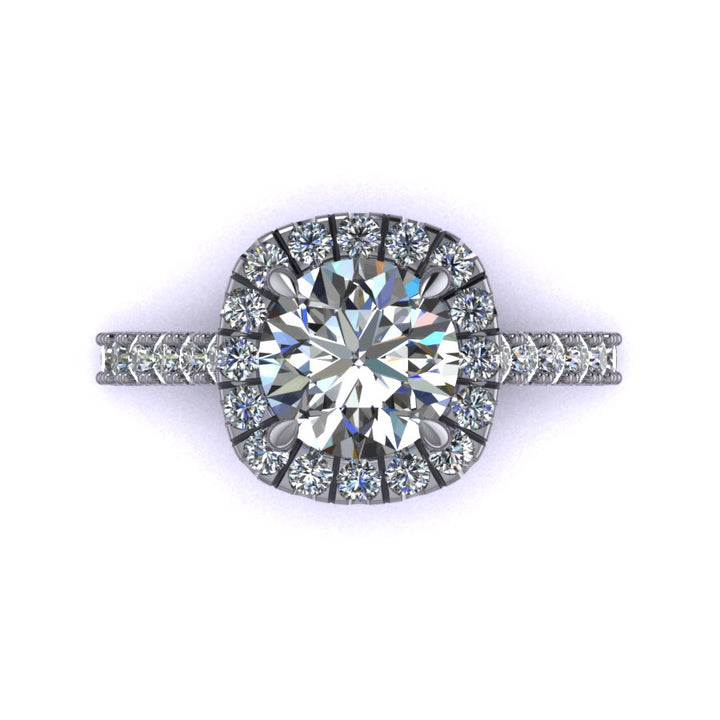 This rendering features a round brilliant center stone set in a soft cushion halo with a diamond basket, diamond bridge, and an elegant cathedral style shank. The diamonds are set in a delicate but durable micro-prong setting style to maximize the brilliance of the diamonds. The height of the halo is medium to high, which helps create the look for more prominence and brilliance, showcasing the center stone best.