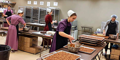 Amish workers making handmade chocolates in a chocolate kitchen.
