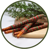 Red and green decorated pretzel rods covered in chocolate.