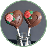 Chocolate heart lollipops with a pink or red rose. Hand molded chocolates from Kalona, Iowa.
