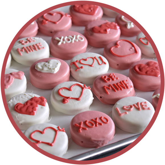 A tray of hand decorated chocolate covered Oreos for valentine's day. Oreos are decorated with hearts, love, and be mine.