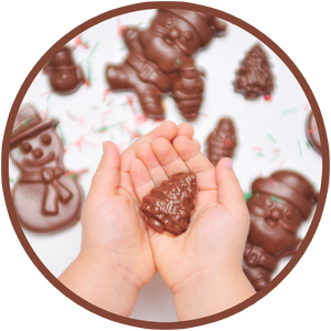 A child holds a mini molded christmas chocolate.