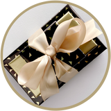 Classy small gift bundle of boxes of chocolate wrapped in gold satin ribbon.
