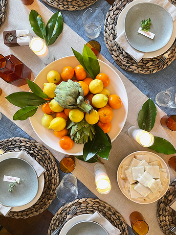 Rustic table scape with lemons, clementines, artichoke, and magnolia leaves