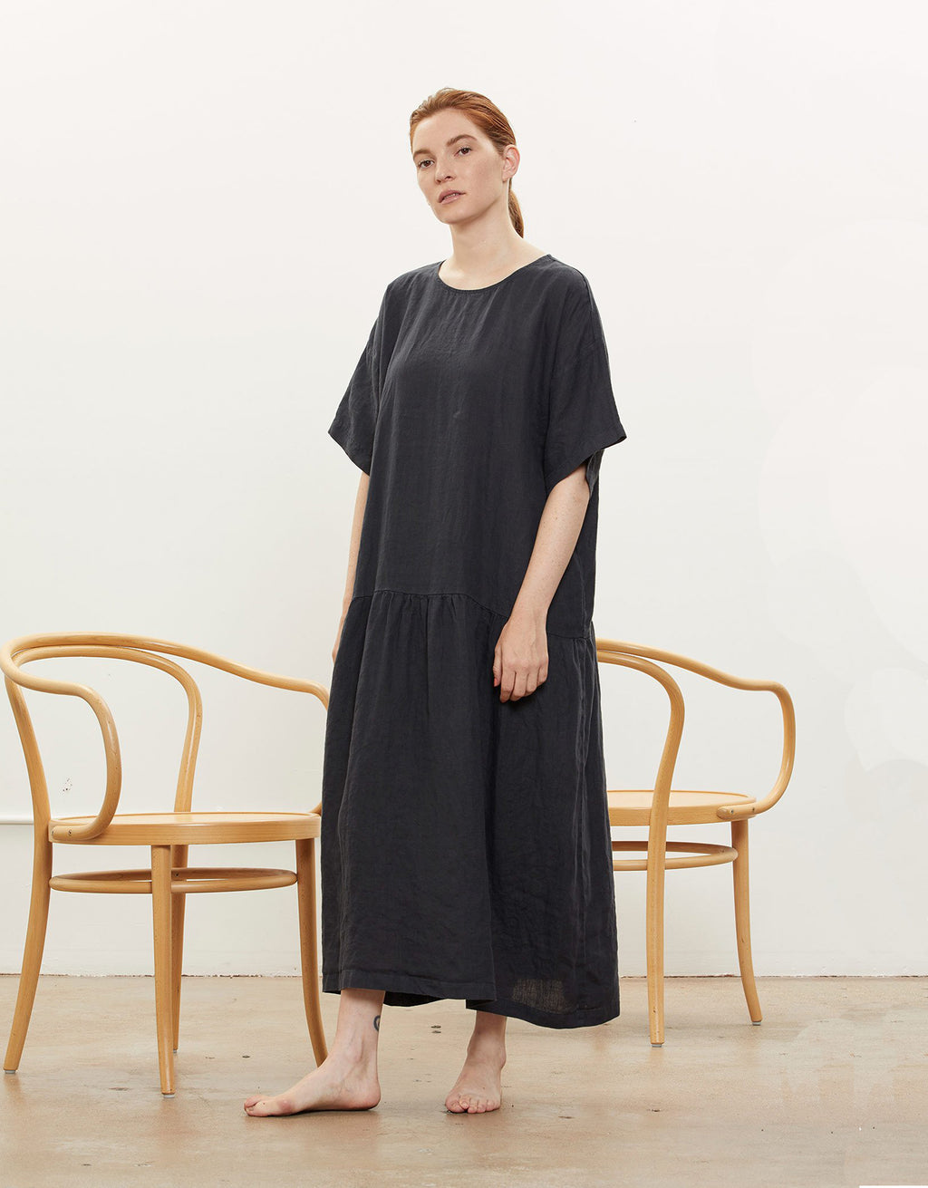 Model wears Black Crane Easy Tee Dress in Black. Available at FAWN Toronto.