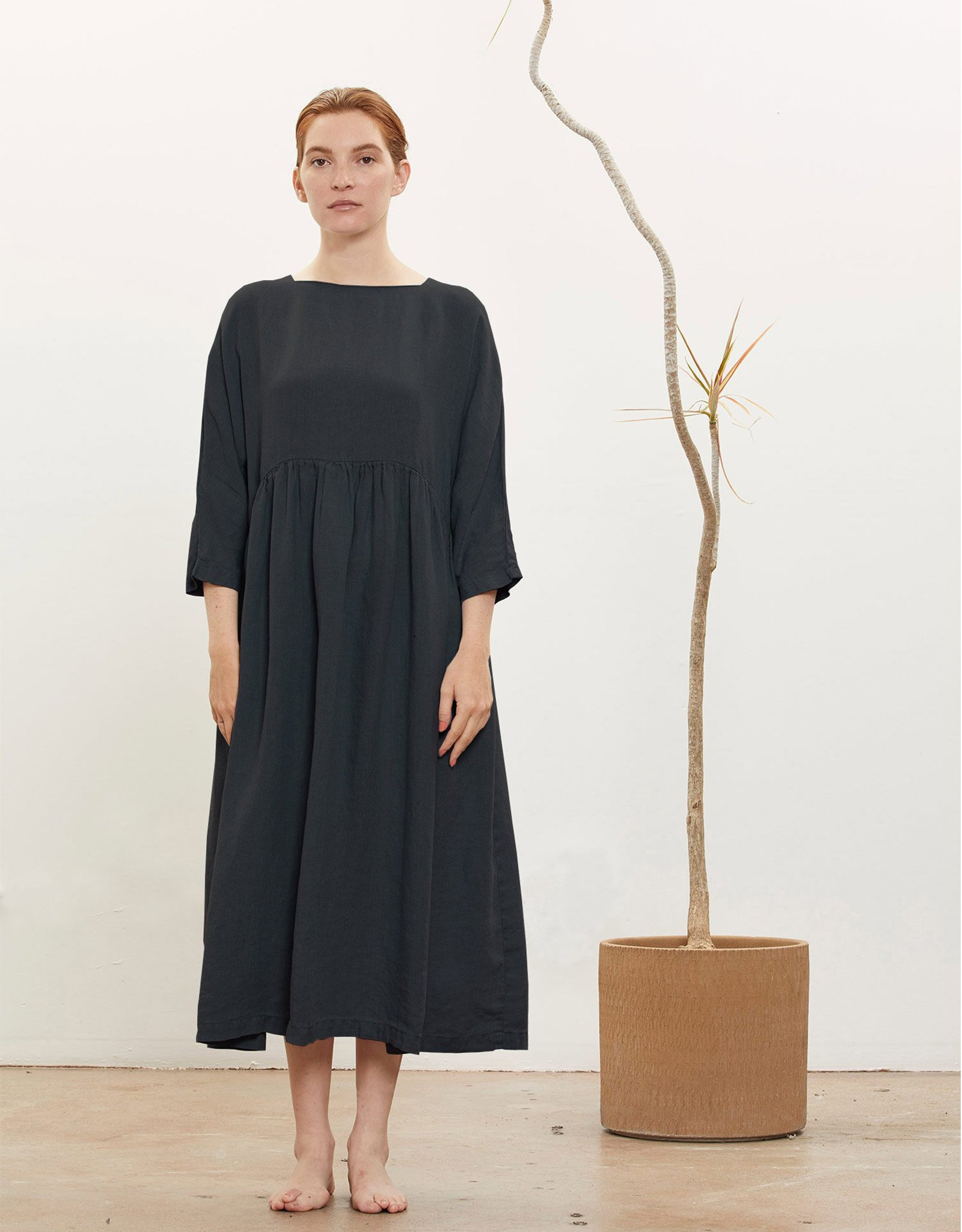 Model wears Black Crane Tradi Dress in Black. Available at FAWN Toronto.