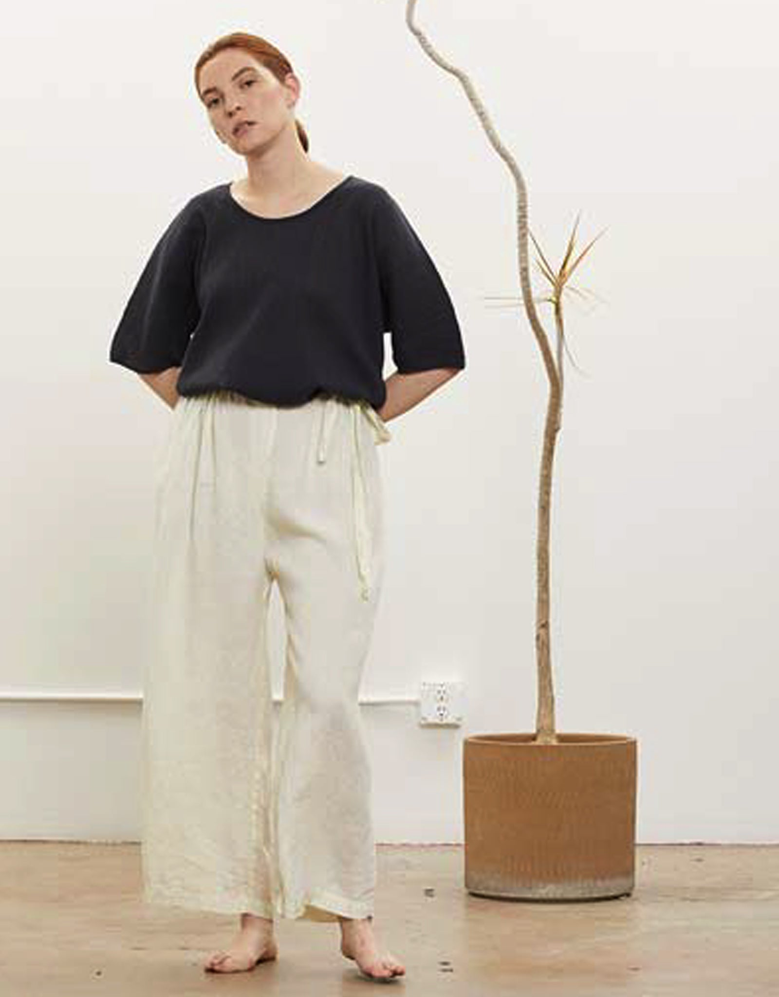 Model wears Black Crane Sack Pant in Cream. Available at FAWN Toronto.