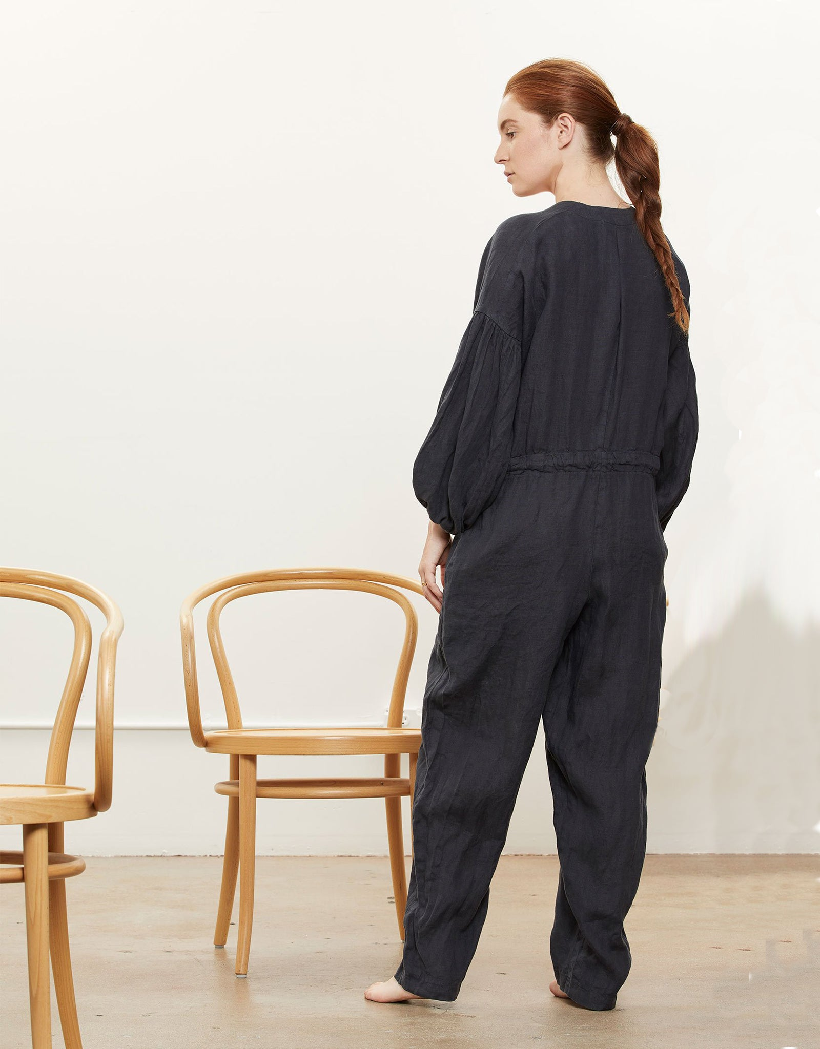 Model wears Black Crane Balloon sleeve jumpsuit in black, back. Available at FAWN Toronto.